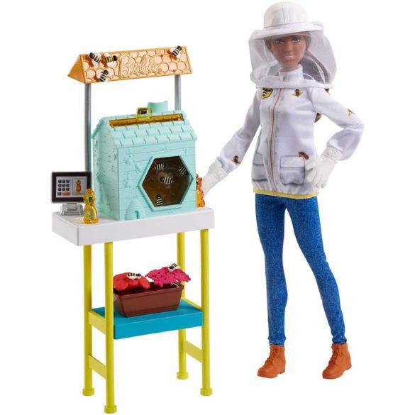 """Pune in scena cele mai fascinante povesti alaturi de papusa Barbie Apicultor si acest set de joaca uimitor Barbie e constienta ca poate realiza orice si e hotarata sa incerce noi meserii si activitati super amuzante! Nu ii este teama de noi provocari si a explorat deja o multime de cariere. Cei mici pot sa descopere aceasta profesie privita pana acum cu o anumita teama si pot invata, alaturi de Barbie, ca si ei pot realiza orice isi propun! Papusa Barbie Apicultor se livreaza alaturi de tot ceea ce ai nevoie pentru o distractie completa - setul de joaca include un stup de albine cu piese ce se misca, albine, floricele si multe altele. Stupul de jucarie si elemente atat de amuzante Apicultorii mentin si ingrijesc coloniile de albine in stupi - locul in care albinele fac mierea atat de delicioasa. De asemenea, acestea sunt folosite pentru a poleniza culturile de fructe si legume sau pentru a produce ceara pentru lumanari sau lotiuni. Cei mici o pot ajuta pe papusa Barbie Apicultor sa duca la bun sfarsit toate sarcinile cu ajutorul stupului atat de frumos colorat ce dispune chiar si de elemente mobile. Actionati cadranul din lateral pentru a observa cu mult entuziasm cum albinele din interior """"zboara"""" sau scoateti fagurele din partea superioara pentru a """"colecta"""" mierea. Elemente si accesorii incantatoare pentru papusa Barbie Apicultor Albinele si ghiveciul cu flori atat de frumoase, in care se pot fixa cu usurinta, te ajuta sa pui in scena polenizarea. Calculatorul si cei doi ursuleti plini parca cu miere te ajuta sa continui distractia. Papusa Barbie zboara prin sarcinile de peste zi purtand o tinuta absolut superba formata dintr-un top tip jacheta decorata cu imaginea unor albinute, pantaloni tip denim, ghetute cu detalii atent realizate, manusi albe si o palarie cu plasa pentru e experienta de joc cat mai reala. Ce gasim in pachetul de livrare? Include papusa Barbie Apicultor cu tinuta si accesoriile prezentate in imagini (inclusiv manusi si palarie alba, cu plasa)"""